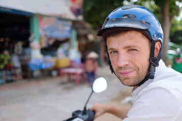 Young man in a helmet stays on a road of Asia watching at the camera.