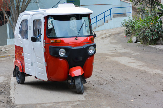 White and red mototaxi on the road.