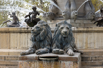 Lions of the Fontaine de la Rotonde in Aix en Provence, France, with fish and swan with angel fountains in the background.