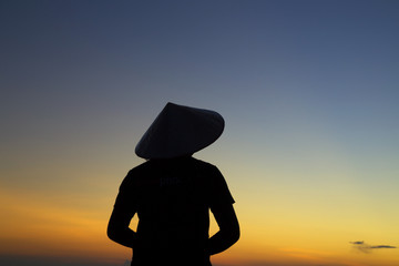 Silhouette woman wear Vietnam hat in sunset on the mountain.