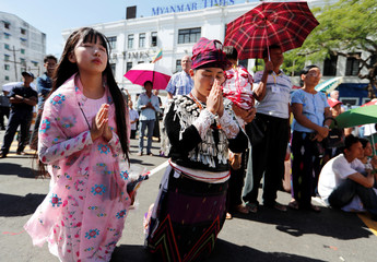 People attend a Mass celebrated by Pope Francis outside St Mary's Cathedral in Yangon