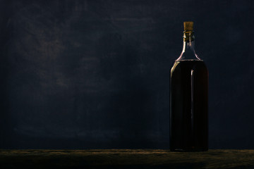 Old bottle with alcohol on a dark background