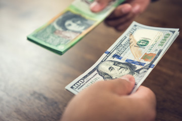 Hand holding US dollar bills trading with Australain dollars