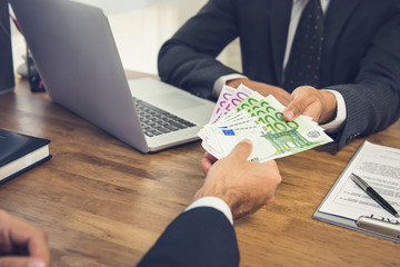 Businessman giving money, Euro banknotes, to his partner while making agreement contract