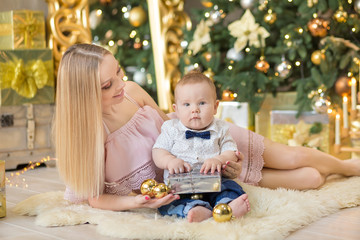 happy family mother and baby little son playing home on Christmas holidays.Toddler with mom in the festively decorated room with Christmas tree. Portrait of mother and baby boy in casual clothes