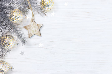wooden star and silver christmas tree branch decorated with glowing light garland on white background
