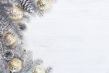 silver christmas tree branches decorated with glowing light garlands and pine cones on white wooden background