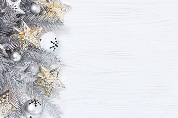 silver christmas fir tree branches with lights garlands and holiday decorations on white wooden background, flat view