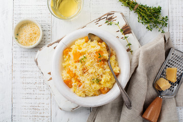 Pumpkin risotto with thyme, garlic, parmesan cheese and white wine on light wooden background. Selective focus. Rustic style. Top view.