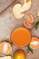 Glass of tangerine juice and fresh peeled fruits