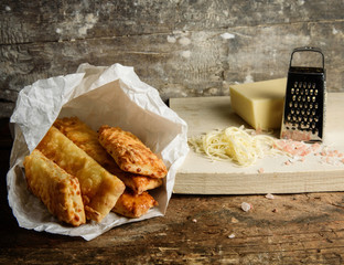 Home baked salty sticks with cheese on rustic wooden background.