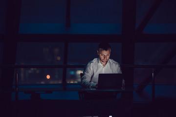 Businessman working on laptop in night office. Fotomurales