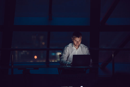 Businessman working on laptop in night office.