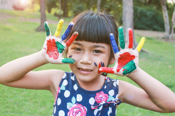 Little asian girl with hands painted in colorful paints ready for hand prints, education, back to school summer and spring concept.