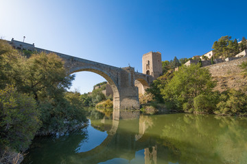 Green water river Tagus, Tajo in Spanish, Alcantara arch bridge and door,  landmark and monument from ancient Roman age, in Toledo city, Spain, Europe