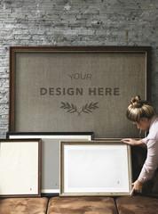 Wall Mural - Woman organizing photo frame mockups