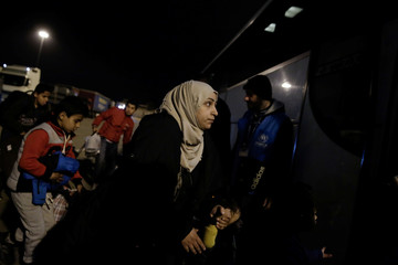 Refugees and migrants board a bus following their arrival on the passenger ferry Blue Star 2 from the island of Lesbos at the port of Piraeus, near Athens