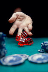Image of man throwing five red dice on table with chips in casino