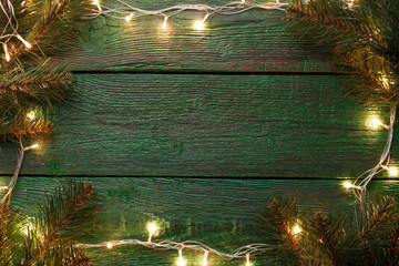 Image of New Year's background with burning garland around perimeter, branches of spruce