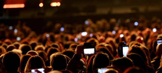people with smart phones at live concert