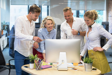 Group of people in office looking at computer