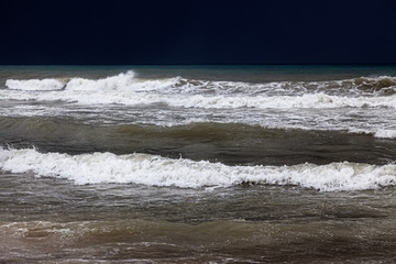 A cloud hangs over the sandy beach