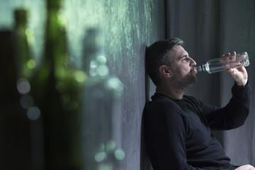 Man wearing black drinking alkohol