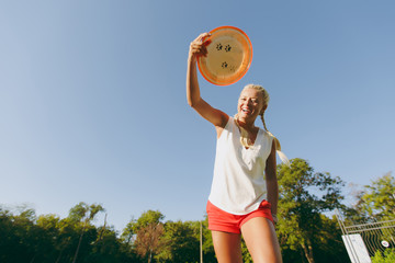 Blonde attractive sporty woman dressed in white T-shirt and orange shorts throwing flying disk to small funny dog, which catching it on the green grass outdoors in park on sky background.