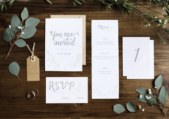 Wedding Invitation Cards Papers Laying on Table Decorate With Leaves