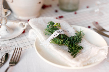 Christmas table: knife and fork, napkin and Christmas tree branch on a wooden table . New Year's decor of the festive table.
