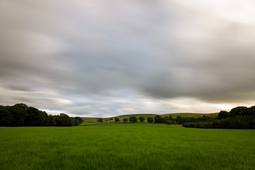 Clouds long exposure over british green countryside England