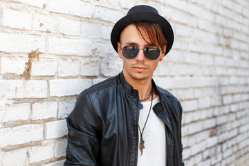 Portrait of a beautiful young man with fashionable sunglasses and a black hat wearing a white shirt and stylish jacket near white brick wall