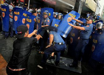 An activist throws a shield at members of the Civil Disturbance Management police during a protest action against President Rodrigo Duterte's plan to set up a Revolutionary Government, along a street in metro Manila