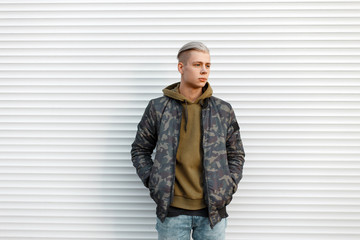 Handsome man in a military jacket with a sweatshirt in jeans near white metal walls