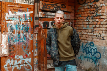 handsome young guy in a stylish military jacket near a wall in the street