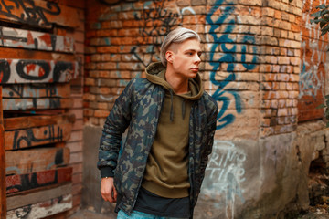 Fashion handsome male model in military jacket near wall