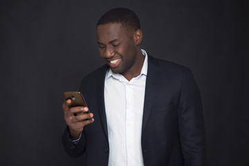 Successful confident black businessman. Handsome african american executive business man holds in hand smart phone.