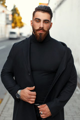 Handsome hipster man with a beard in a black trendy coat in the autumn day on the street