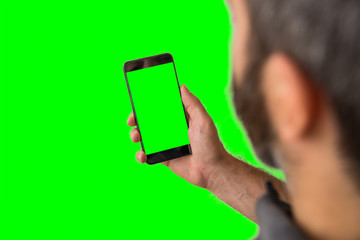 Young adult man hand holding green screen smartphone on green screen background.