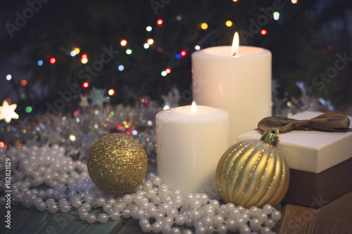 a festive still life with two burning white candles of different size a brown and