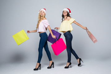 Two girls wearing Christmas hat with bags on white background isolated