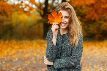 Portrait of a beautiful happy woman with a smile with an autumn yellow leaf in the park