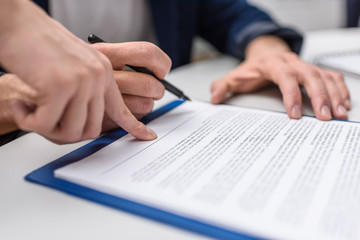 cropped shot of client signing contract while manageress pointing at it