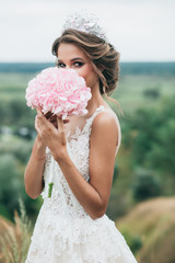 The bride is holding a wedding bouquet of hydrangeas and stands on a hill overlooking a beautiful nature. Closes his face with a wedding bouquet.