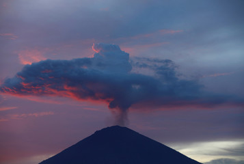 A plume of smoke above Mount Agung volcano is illuminated at sunset as seen from Amed, Karangasem Regency, Bali,