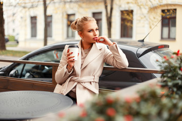 Beautiful young woman in a stylish autumn coat drinking coffee and sitting in a cafe on the outdoors