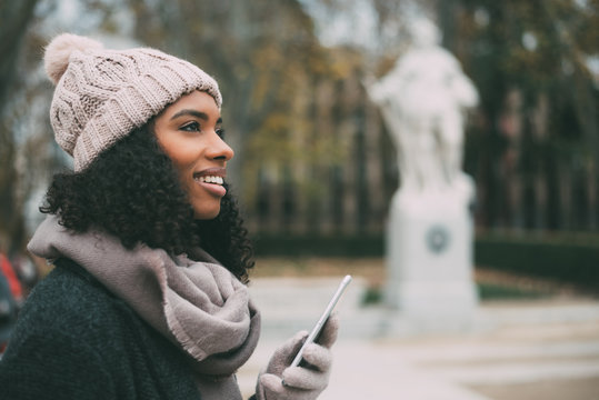 Young black woman on the mobile phone near the royal palace in winter .