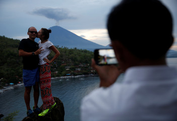 Tourists from Russia pose while having their photograph taken with Mount Agung volcano erupting in the background from Amed, Karangasem Regency, Bali