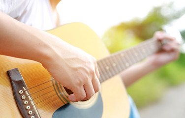 Guitar player playing song outdoor.