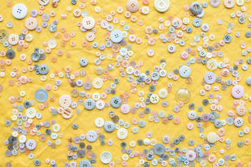 top view of scattered colorful buttons on yellow cloth background